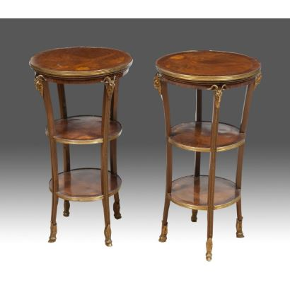 Muebles. Pareja de mesitas auxiliares en madera, compuestas por tres tableros circulares unidos por cuatro patas decoradas con cabezas de carnero en bronce dorado. Medidas: 75x40x40cm.