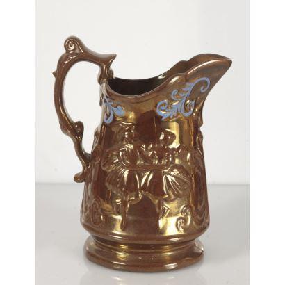 Cerámica. Jarra con un asa realizada en cerámica dorada de Bristol, con decoración de personajes en bajo relieve y motivos en azul. 21x17cm.