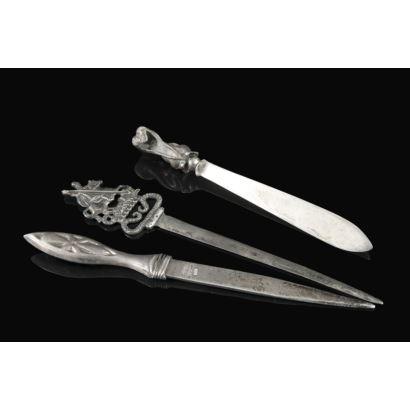 Plata. Conjunto formado por tres abrecartas de plata. Representan a una ardilla con bellota, San Jorge y el dragón, y Cruz de Santiago. Largura mayor 16 cm.
