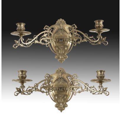 Objetos. Pareja de apliques en bronce dorado, siglo XX. Dos brazos articulados decorados con roleos. Pequeño copete de venera. Medidas: 21 x 38 cm.