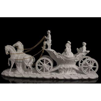 Magnífico biscuit en el que vemos un bonito carro tirado por dos caballos con riendas doradas, alberga las figuras de dos adultos y dos niños elegantemente ataviados. Medidas: 46x93x25cm.