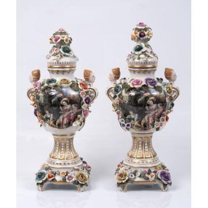 Pareja de jarrones en porcelana esmaltada con decoración floral en relieve, decorados en cuerpo central con escenas  sobre fondo blanco.