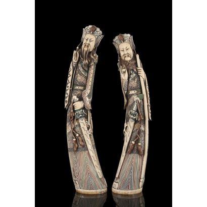 Importante pareja de tallas de marfil policromadas, representan a dos guerreros chinos con espadas, están ricamente ataviados con tocados y túnicas. Con certificado de antigüedad. Alto: 64cm y 61cm.