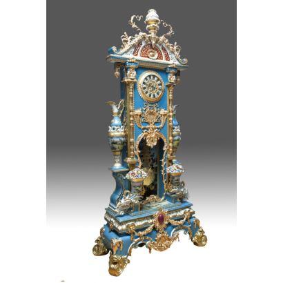 Gran reloj con péndulo realizado en porcelana policromada y dorada, con ricos apliques en bronce dorado y decoración de cornucopias florales y jarrones, presenta escenas arquitectónicas pintadas a mano. S.XX.