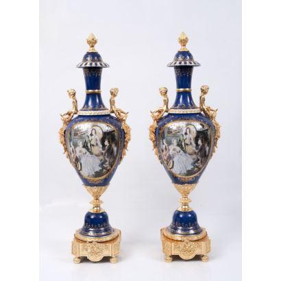 Pareja de jarrones en porcelana policromada y esmaltada sobre fondo azul, con pie cuadrado y asas de niños en bronce dorado, con escenas centrales: