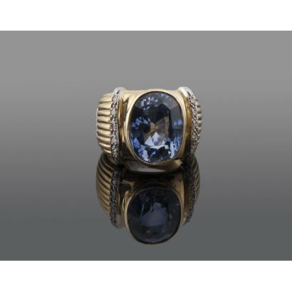 Sortija estriada de oro amarillo con piedra oval azul flanqueada por dos hileras con brillantes que suman aprox 0,20cts. Diámetro: 16mm. Peso: 9,9g.
