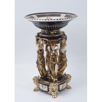 Centro de mesa en porcelana policromada y dorada, compuesto por cuerpo inferior con cabezas doradas de carnero y cuatro Cariátides con túnicas doradas que sujetan plato superior, con fondo azul  y blanco. Marca en base. Medidas: 51,5x35,5cm.