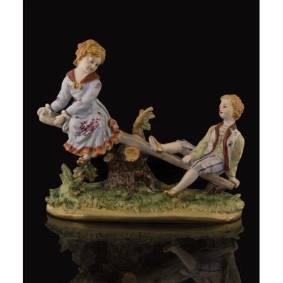 Bonita figura de porcelana policromada de Dresden, en ella un balancín en el que juegan dos niños ricamente ataviados. Marca en base. 25x10x22cm.