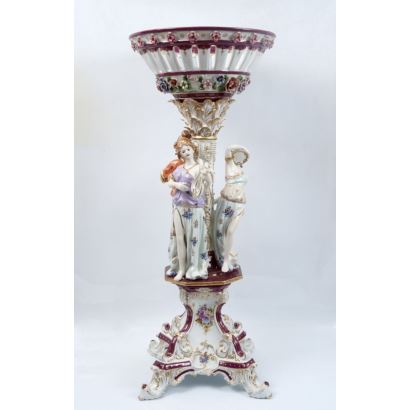 Centro de mesa en porcelana policromada en granate y blanco, con decoración de mujeres clásicas con instrumentos, cuerpo superior con cuenco calado. Marca en base. Medidas: 105x43,5cm.