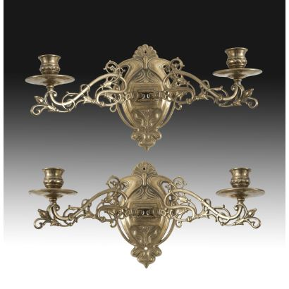 Pareja de apliques en bronce dorado, siglo XX. Dos brazos articulados decorados con roleos. Pequeño copete de venera. Medidas: 21 x 38 cm.