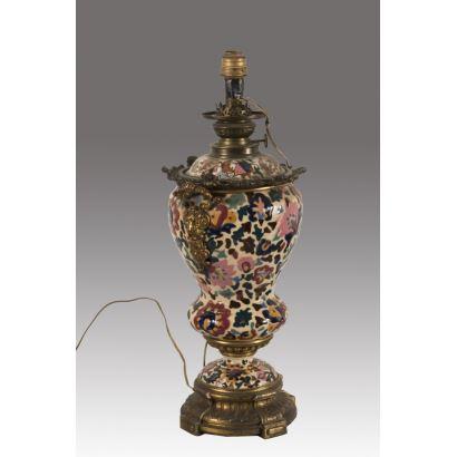 Bonito quinqué del s.XIX reconvertido en lámpara, presenta rica decoración floral con apliques en pie y asas de bronce dorado. Medidas: 54x20cm.