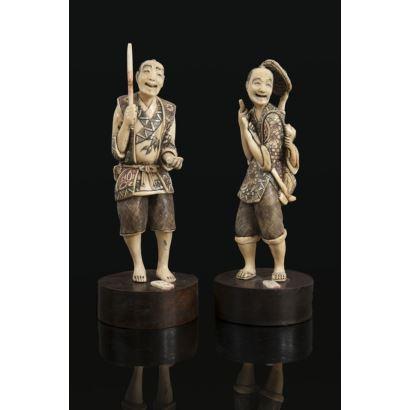 Pareja de figuras costumbristas orientales talladas en marfil sobre peana circular de madera.