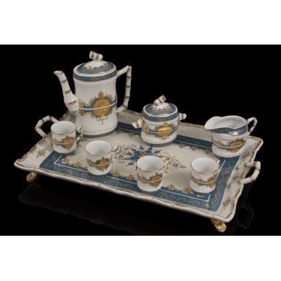 Original juego de café en porcelana en azul y dorado sobre fondo blanco, presenta asas imitando bambú  y bonita decoración floral, consta de bandeja, cafetera, azucarero, jarra y tazas.