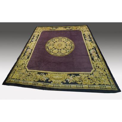 Alfombra Española de lana con motivos dorados en medallón central y bordes principales contrastando con el campo violeta. Firma en esquina MADRID. 470X440cm
