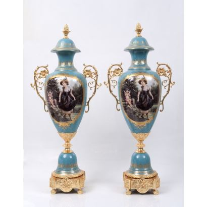 Pareja de jarrones en porcelana policromada y esmaltada, con pie y asas de roleo en bronce dorado, con escenas centrales sobre fondo azul: