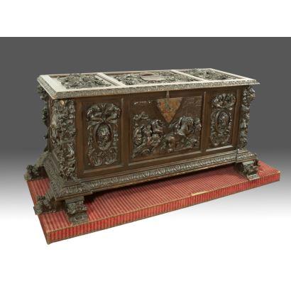 Arcón en madera tallada y cierre de forja con llave, con excepcional decoración heráldica en tapa y cuerpo con escena bélica flanqueada por mascarones. Medidas: 85x185x60cm.