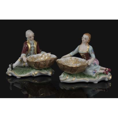 Pareja de almendreros en porcelana policromada, representan a una pareja de hombre y mujer vestidos a la moda dieciochesca sentados sobre el césped. Medidas: 15x17x11cm.