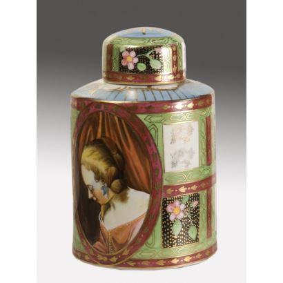 Bello tarro con tapa realizado en porcelana policromada, la pieza con cuerpo cilíndrico está ricamente decorada con diversos motivos, entre los que destacan dos óvalos con el retrato de una dama y un paisaje, ambos sobre fondo verde y dorado. 15x10cm.