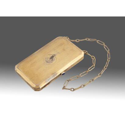 Bolsito polvera con espejo realizado en bronce dorado y placa de marfil interior, presenta iniciales grabadas en tapa, asa de cadena. Siglo XIX. Medidas: 8,5x5x1cm.