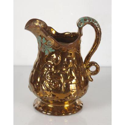 Bonita jarra realizada en cerámica dorada de Bristol, con bonita decoración en relieve y detalles pintados en verde. (Restaurada). 20x16cm.