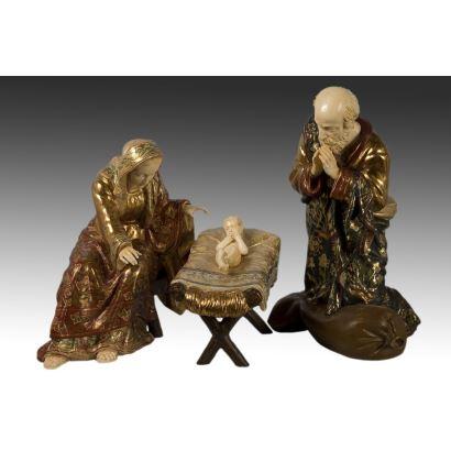 Grupo escultórico de marfil y madera policromada, representando el nacimiento y adoración del niño Jesús.