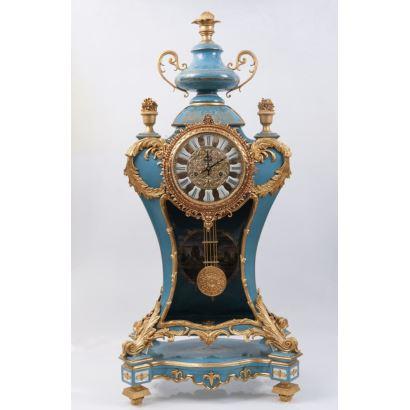 Reloj de sobremesa realizado en porcelana policromada en azul, presenta delicada decoración floral en laterales y apliques en bronce dorado que forman numerosas rocallas, está rematado en copa clásica. Medidas: 110x53x35cm.
