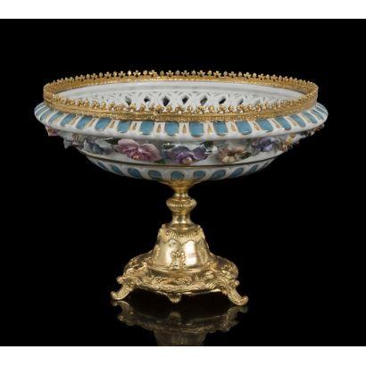 Elegante copa en porcelana policromada en azul y blanco con motivos florales, se alza sobre pie en bronce dorado al oro fino. Medidas: 23,5x32,5cm.