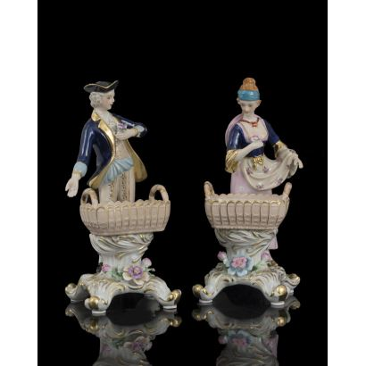 Bonita pareja de figuras de porcelana policromada, representan a un hombre y una mujer de gusto galante vestidos a la moda del siglo XVIII,  ambos portan cestas en la parte frontal. Medidas: 26x11x11cm.