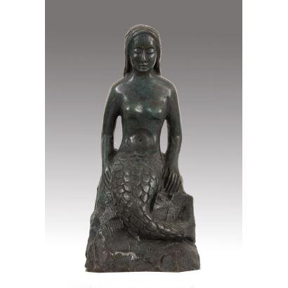 Figura realizada en metal pavonado en la que contemplamos la imagen de una sirena posada sobre unas rocas. 29x13x13cm.