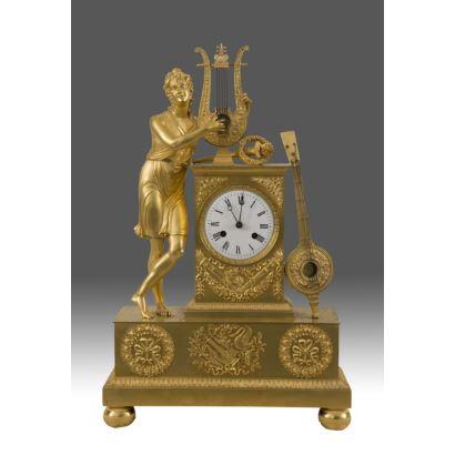 Importante reloj estilo Imperio, en bronce dorado donde destaca la escultura de un personaje clásico tocando un arpa. Siglo XIX.  52x34x12cm