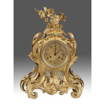 Importante reloj de sobremesa Luis XV, en bronce dorado al oro fino, con sinuosa decoración de roleos vegetales, remata la pieza un ramo de flores. ss.XVIII-XIX. Medidas: 47x36x16cm.