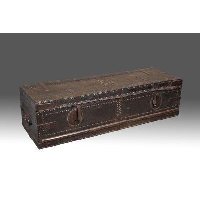 Antiguo arcón de viaje realizado en madera y cubierto en cuero tachuelado con guarniciones en hierro, presenta las iniciales S.G. bajo corona en tapa. SS. XVIII-XIX. Medidas: 48X148X41cm.
