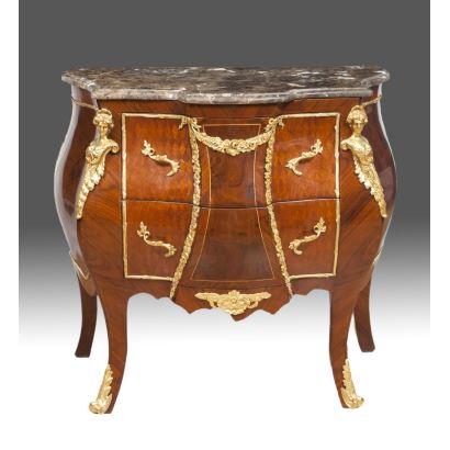 Cómoda de inspiración Luis XV realizada en madera con tablero de mármol jaspeado y elegantes apliques en bronce dorado, cuenta con dos cajones frontales y cuatro patas curvas. Medidas: 78x80x48cm.