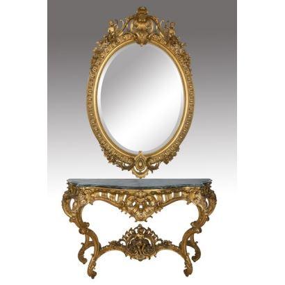 Muebles. Extraordinaria Consola y Espejo Rococó, estilo Luis XV. Observamos preciosistas tallas de roleos con rocallas y amorcillos en el espejo ovalado y en las patas rocaille, doradas de la consola de superficie marmórea verde. Siglo XIX