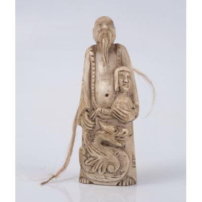 Curioso netsuke tallado en colmillo de marfil, representa a un personaje alegórico oriental masculino con larga trenza y túnica sujetando busto de personaje, destaca la figura de dragón chino enroscado a sus pies. Medidas: 13x4cm.