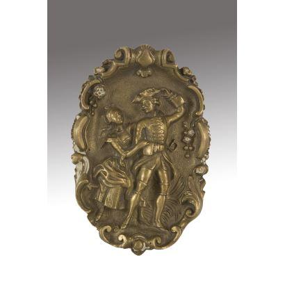 Medallón realizado en bronce dorado, muestra en bajo relieve a una pareja de enamorados de gusto historicista. Medidas: 12x8cm.
