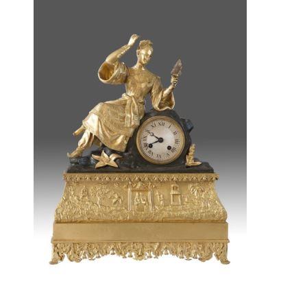 Reloj de sobremesa en bronce dorado y patinado, cuenta en la parte superior con figura de dama oriental sobre esfera y cuerpo inferior con friso de chinerías. Francia, siglo XIX. Medidas: 44x33x13cm.