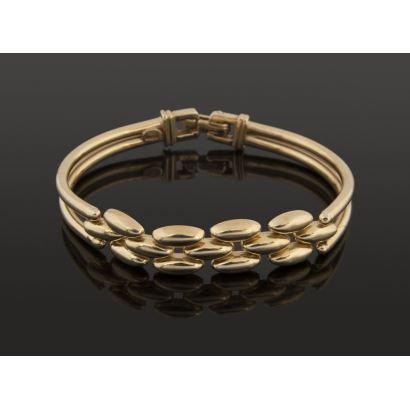 Elegante pulsera de oro amarillo, alterna pulsera rígida con frontis articulado. Peso: 23,5g.