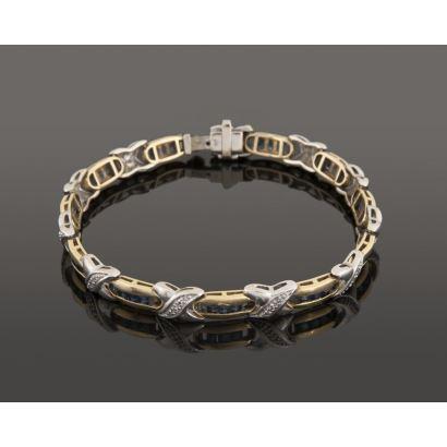 Pulsera articulada en oro amarillo y oro blanco, alberga numerosos zafiros en talla princesa dispuestos en carril y brillantes. Total brillantes aprox: 0,11cts. Peso: 21,8g.