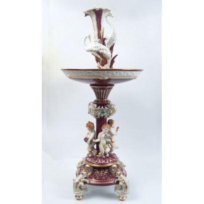 Fuente realizada en porcelana policromada con fondo granate y blanco, pie con rocalla y astil de ángeles, rematada por garzas y copa con bola giratoria. Medidas: 120x50x50cm.
