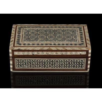 Joyero con estructura de madera con forma rectangular, está decorado con taracea de nácar, ébano y hueso que forman motivos coptos, árabes y judíos, con interior forrado en terciopelo. 16x10cm.