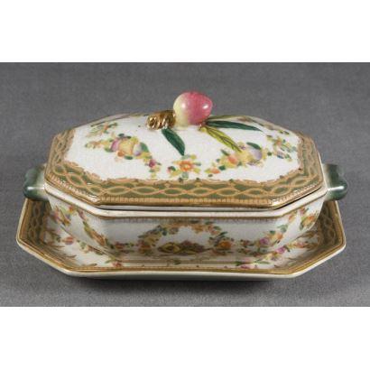 Porcelana. Bella salsera con plato y tapa ricamente decorados con motivos florales y frutales de la casa