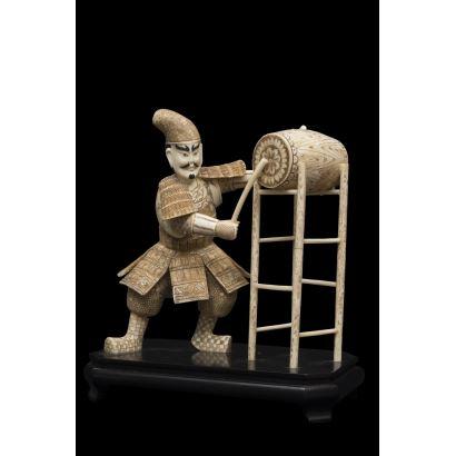 Magnífica figura en hueso en la que contemplamos a un guerrero chino tocando un tambor ceremonial, la pieza de gran realismo se alza sobre peana de madera. Medidas: 32x28x16cm.