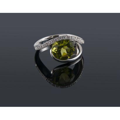 Gran anillo de oro blanco de 18K  con un diseño moderno que alberga en su centro un bonito peridoto de variedad olivino acompañado por 20 diamantes de talla brillante. Peso: 8,46 gr.