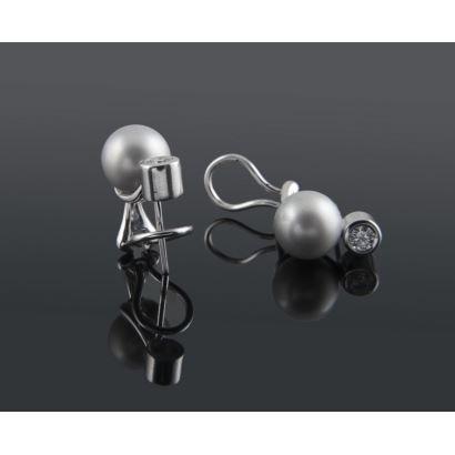 Elegantes pendientes de oro blanco 18K con dos perlas gris claro de 9,50 mm cada una, bajo chatones que albergan dos diamantes talla brillante de 0,20 quilates cada uno. Cierres omega. Total diamantes 0,40 quilates. Peso: 8,90 gr.