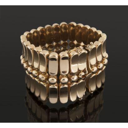 Importante pulsera articulada realizada en oro amarillo de 18k, presenta motivos  circulares y ovales. Peso: 88,9g.