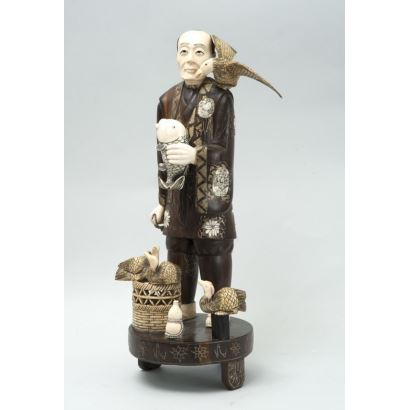 Figura criselefantina costumbrista tallada en madera con incrustaciones de marfil. China, pricipios s.XX.