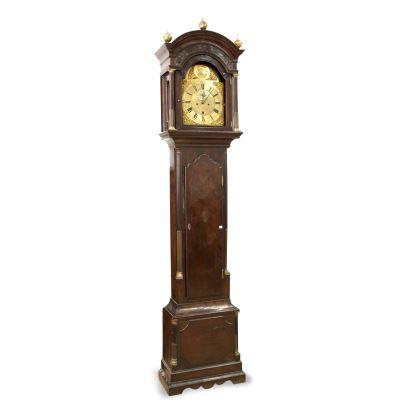 Relojes. Reloj de caja alta inglés, S. XVIII. Presenta caja en madera de caoba con aplicaciones de bronce. Firmado en la esfera John Higgs. Con pesas y péndulo en estado de marcha. Con llave. Medidas: 249 x 55 x 26 cm.