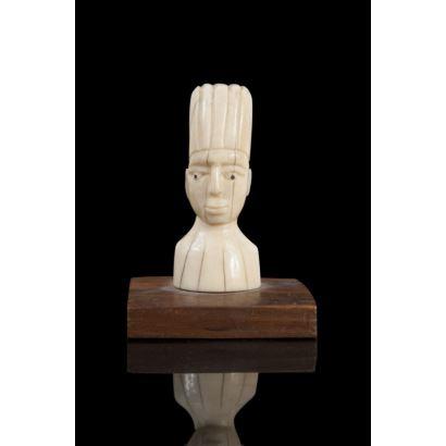 Arte Africano . Busto masculino con tocado tallado en marfil sobre peana de madera. Medida sin peana: 9cm c/p 11cm.