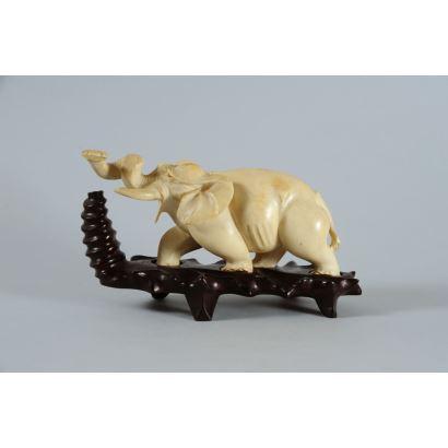 Figura tallada en marfil sobre base de madera, representa a un elefante con la trompa en alto enroscada. Con certificado de antigüedad. Largo sin peana: 17cm.